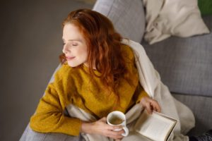 Attractive young redhead woman with a blissful smile relaxing at home during winter sitting warmly wrapped in a blanket on the sofa with a mug of hot tea and a book
